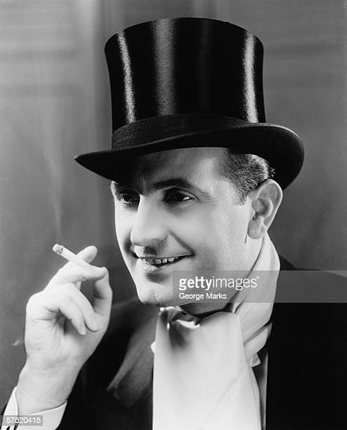 Man in top hat smoking cigarette, (B&W), portrait