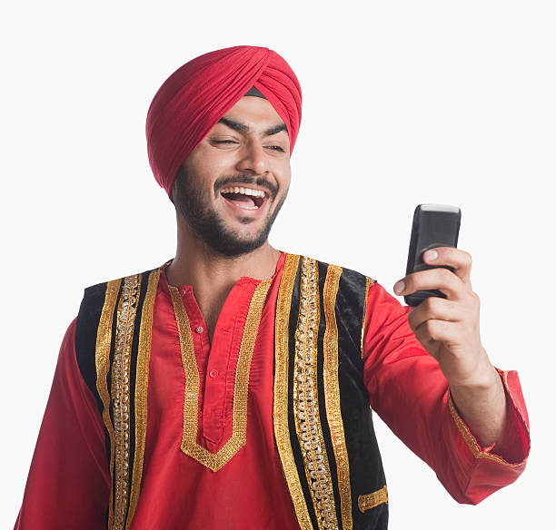 Man in traditional clothing looking at a mobile phone and laughing