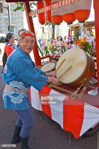 Man in traditional costume beating drums
