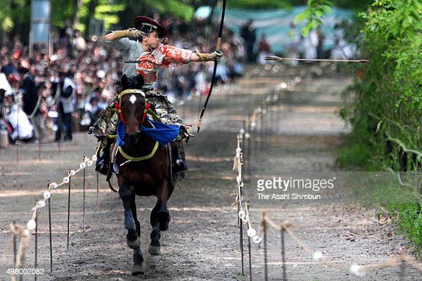 A man in traditional costume on a horseback takes aim at a target during the Yabusame ritual ahead of the Aoi Festival at Shimogamo Shrine on May 3...