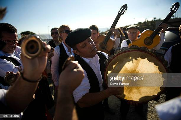A man in traditional costume plays a tambourine with his 'Panda' as they rehearse before performing in a traditional Verdiales Flamenco contest on...