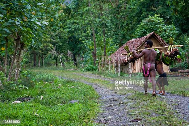 A man in traditional dress carries home freshly harvested taro from the garden A small girl accompanies him and peeks a smile at the camera In the...
