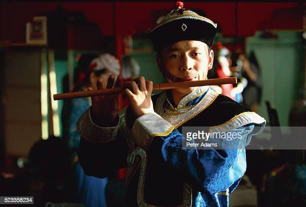 man in traditional dress playing flute - モンゴル ストックフォトと画像
