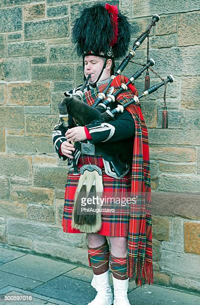 Man in traditional Scottish dress playing bagpipes in Edinburgh
