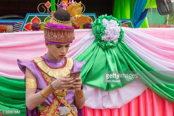 man in traditional thai clothes using his phone. - tim bewer fotografías e imágenes de stock