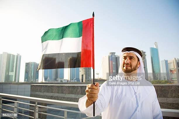 Man in traditionally Middle Eastern attire proudly holding UAE flag, Dubai cityscape in background, UAE