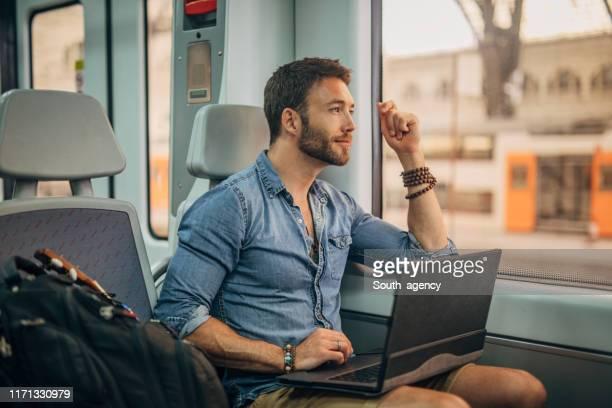 hombre en tren trabajando en portátil - tren fotografías e imágenes de stock