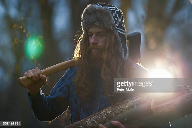 Man in trapper hat chopping wood in countryside