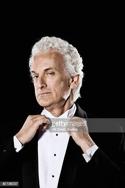 Man in tuxedo adjusting bow tie