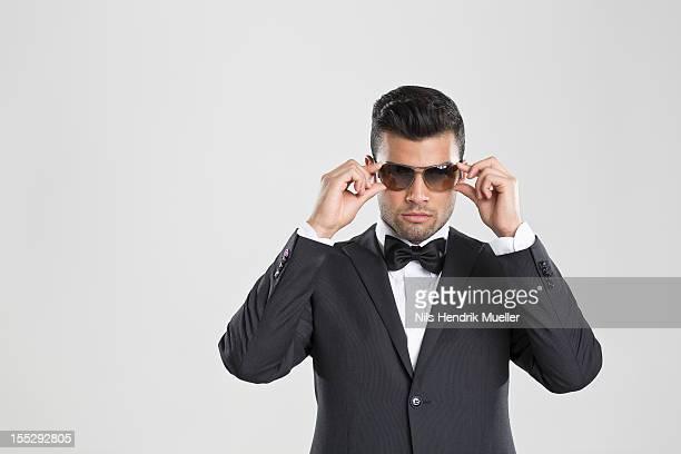 Man in tuxedo adjusting his sunglasses