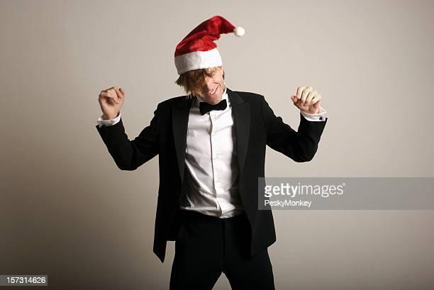 Hombre en mespilia celebrar días festivos bailando con gorro de papá noel