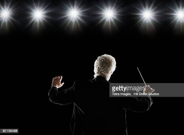 Man in tuxedo conducting under lights