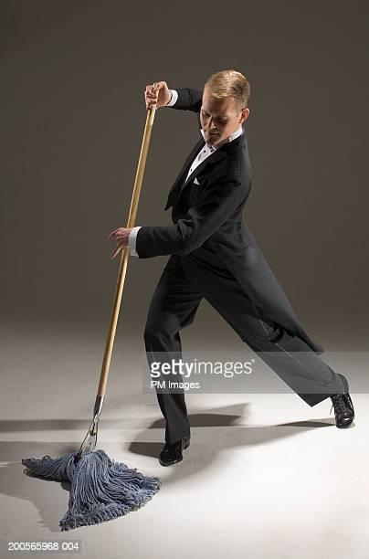 Man in tuxedo dancing with mop