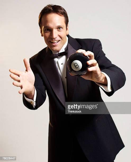 Man in tuxedo holding magic eight ball.