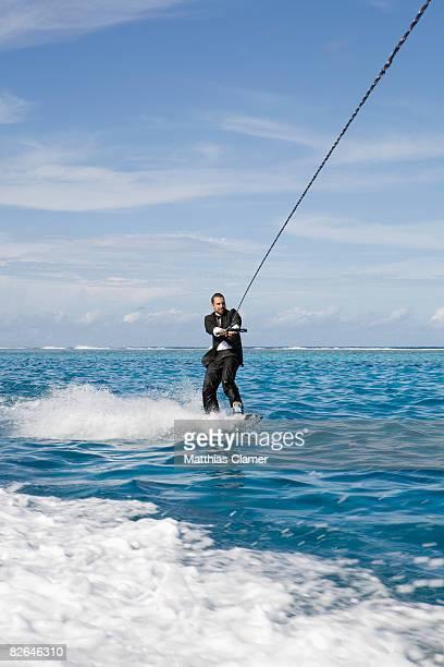 man in tuxedo is wakeboarding