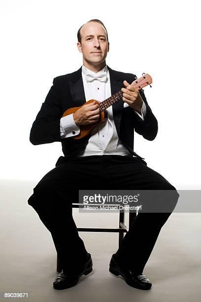 man in tuxedo playing the ukulele - smoking stock-fotos und bilder