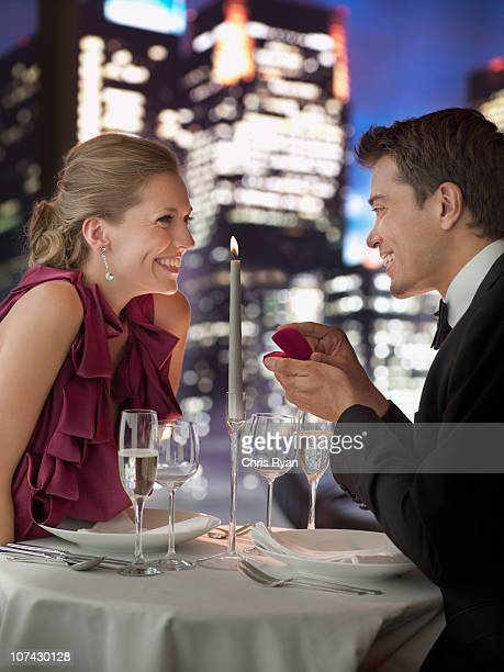 Man in tuxedo proposing engagement to girlfriend