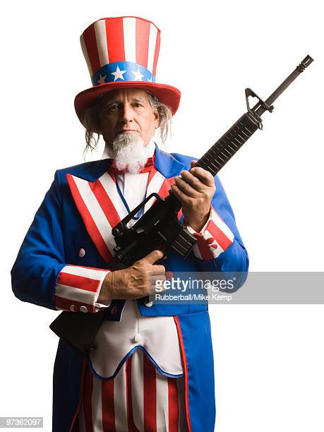 Man in Uncle Sam's costume with gun, studio shot