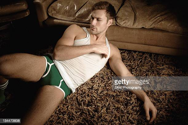 Man in underwear lying on the floor in front of a leather sofa