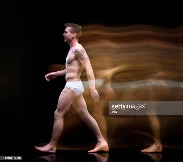 man in underwear moving around creating a blur image - black men in speedos stock photos and pictures