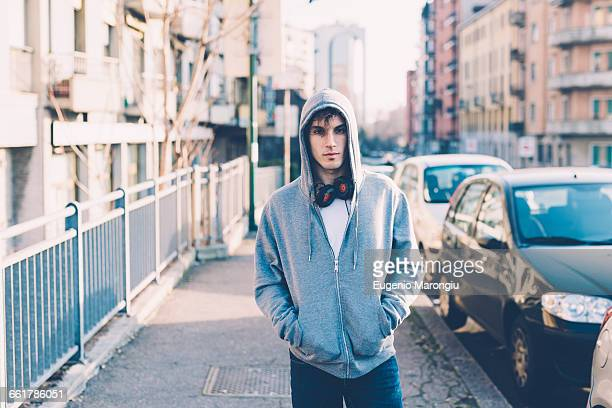 man in urban area wearing hooded top and headphones looking at camera - hoodie headphones stock pictures, royalty-free photos & images