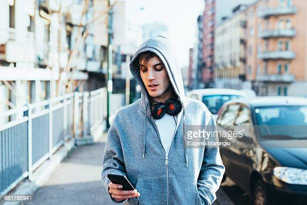 man in urban area wearing hooded top and headphones looking down at smartphone - hooded shirt stock pictures, royalty-free photos & images