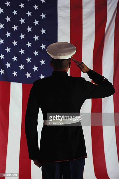 man in u.s. marine corps uniform saluting american flag - marines stock pictures, royalty-free photos & images