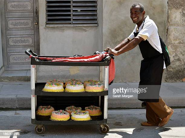 Man in Versalles, Matanzas, Cuba delivers elaborately iced cakes on a trolley. He is pushing the trolley down the street in the sun. Raul Castro's...