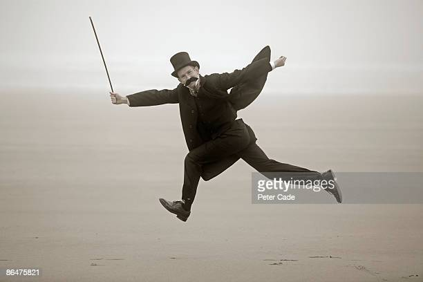 man in victorian dress jumping on beach - 19th century style stock pictures, royalty-free photos & images