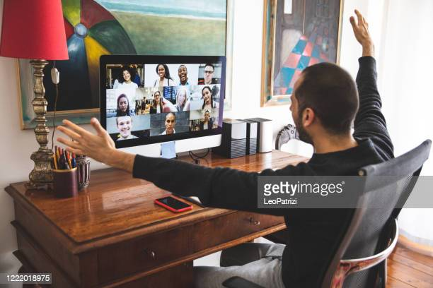 man in video call with friends and relatives in front of computer - video still stock pictures, royalty-free photos & images