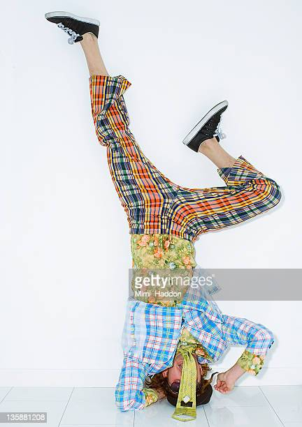 man in vintage clothing doing a headstand - fashion oddities stock pictures, royalty-free photos & images