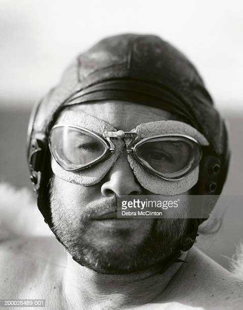 Man in vintage flight goggles and leather cap, close-up, (B&W)