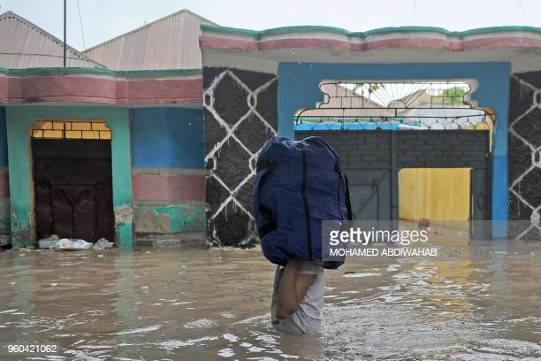 A man in waist deep flood water carries belongings at Wadajir district of Mogadishu on May 20 2018 after homes were inundated in Somalia's capital...
