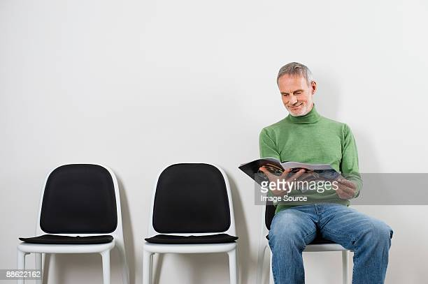 man in waiting room - picture magazine stock pictures, royalty-free photos & images