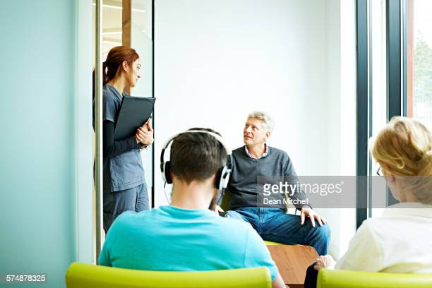 Man in waiting room talking with nurse