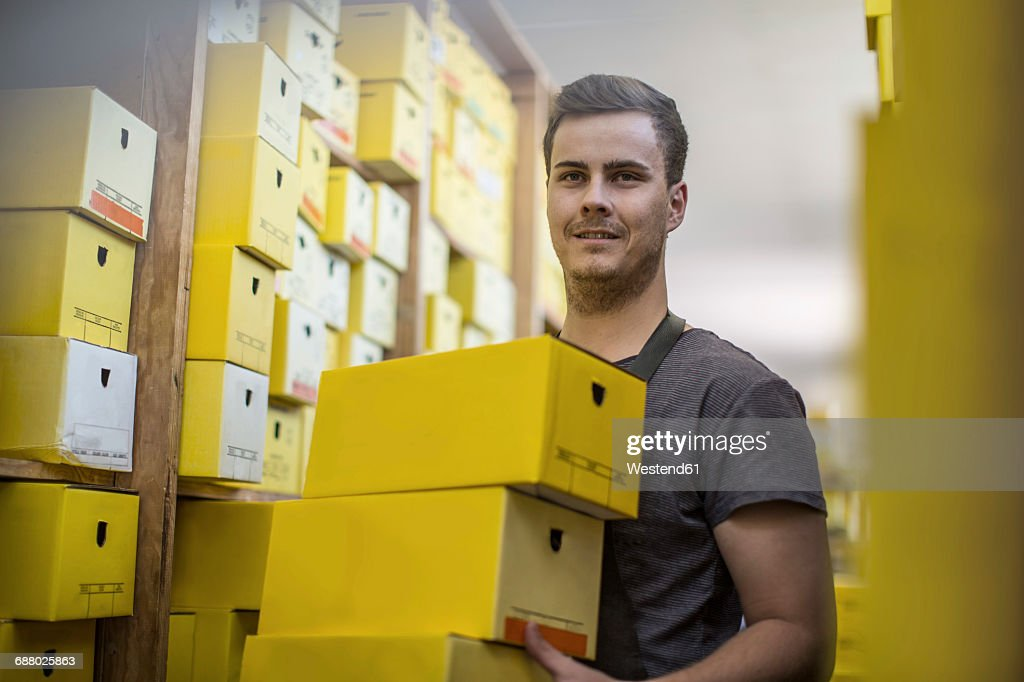 Man in warehouse carrying shoe boxes : Stock Photo