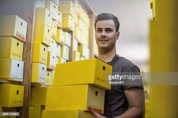 Man in warehouse carrying shoe boxes