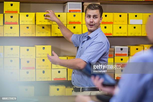 Man in warehouse with shoe boxes talking to customer