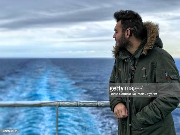 man in warm clothing leaning on railing while traveling on boat at sea - carmelo ストックフォトと画像