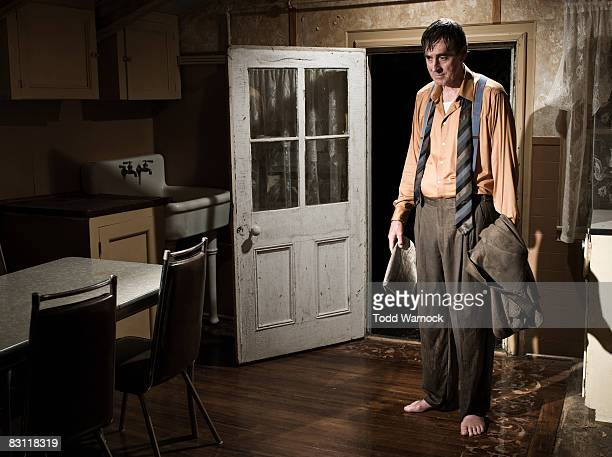 man in wet clothes standing in kitchen
