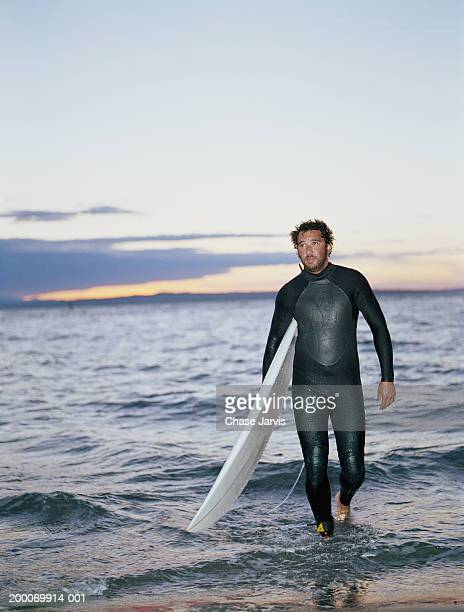 Man in wet suit walking out of water carrying surfboard, sunset