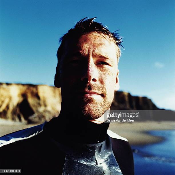 Man in wetsuit on beach, close-up