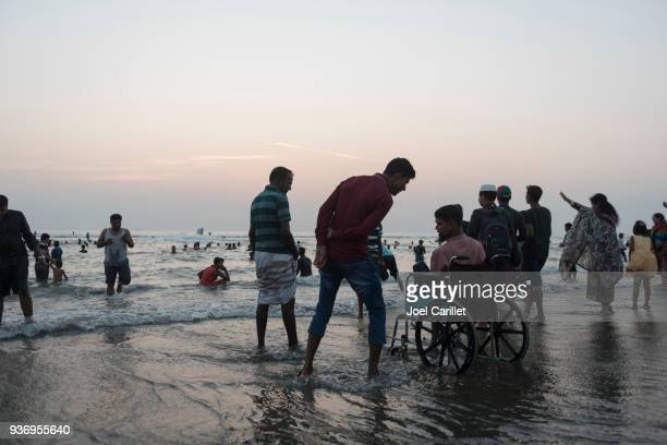 man in wheelchair at beach in cox's bazar, bangladesh - cox bazar sea beach stock pictures, royalty-free photos & images