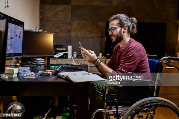 man in wheelchair at home - wheelchair stock pictures, royalty-free photos & images