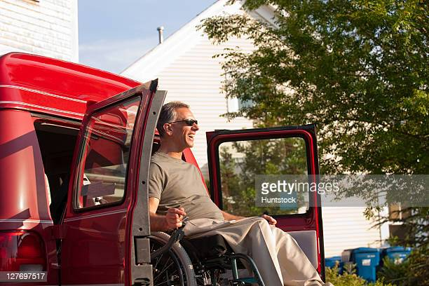 man in wheelchair being lowered from accessible van - disabled access stock photos and pictures