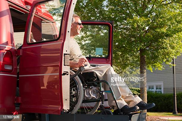 man in wheelchair being lowered from accessible van - assistive technology stock photos and pictures