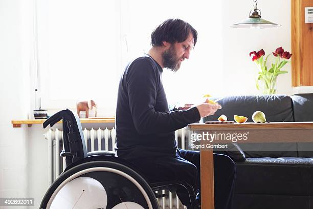 Man in wheelchair cutting fruit