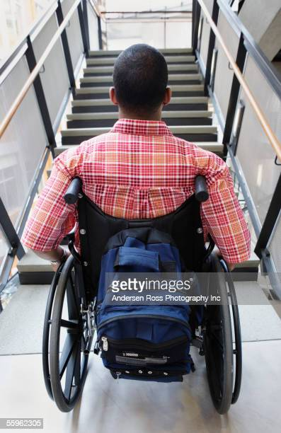 man in wheelchair looking at stairs - prejudice stock pictures, royalty-free photos & images