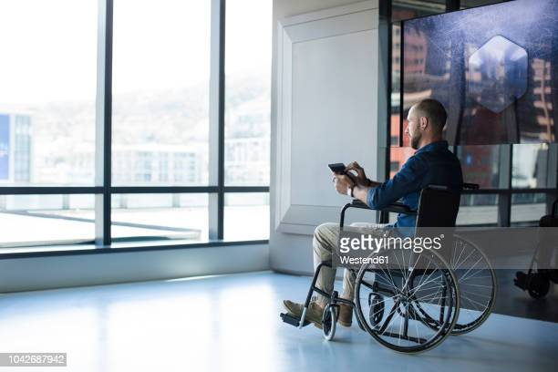 man in wheelchair looking out of window in office, using tablet - cadeira de rodas imagens e fotografias de stock