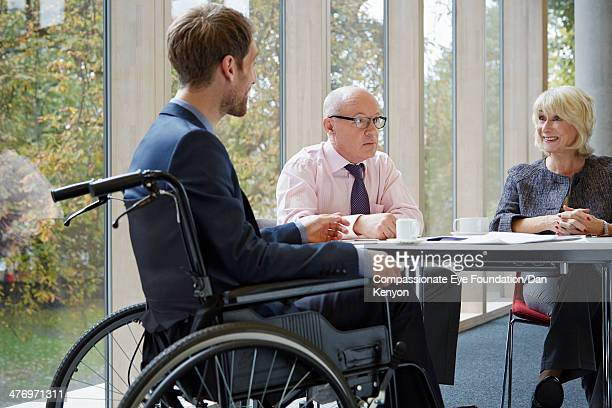 Man in wheelchair meeting with colleagues